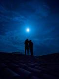 夫妇剪影在一个屋顶的在满月下 免版税库存图片