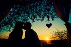 夫妇剪影在亲吻在日落的爱的 免版税库存图片