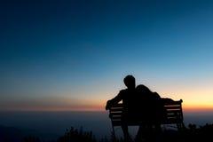 夫妇剪影在日落背景中坐并且拥抱 免版税库存照片