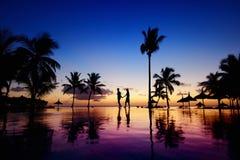 年轻夫妇剪影在风景日落的 库存图片