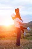 夫妇剪影愉快在风景山雾和太阳 免版税库存图片