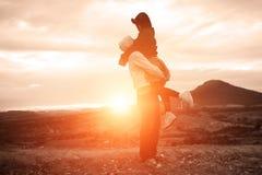 夫妇剪影愉快在风景山雾和太阳 免版税库存照片