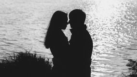 夫妇剪影由水的 免版税库存照片
