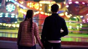 夫妇剪影,站立回到照相机和吸引力观看的自转在游乐园 恋人 股票视频