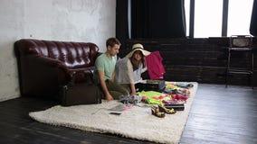 年轻夫妇包装材料到手提箱里在家 股票录像