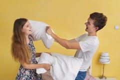 年轻夫妇十几岁,枕头战 图库摄影