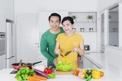 年轻夫妇厨师沙拉在厨房里 免版税库存照片
