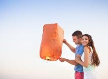 年轻夫妇发动一个红色中国天空灯笼 库存照片