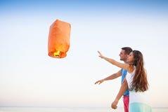 年轻夫妇发动在黄昏的一个红色中国天空灯笼 免版税库存照片