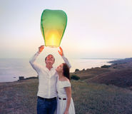 年轻夫妇发动在黄昏的一个绿色中国天空灯笼 免版税库存图片