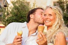 夫妇吃冰淇凌亲吻愉快 免版税图库摄影