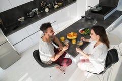 年轻夫妇吃早餐在厨房,亚裔妇女和拉美裔人早晨吃 库存图片