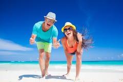 夫妇后面看法在明亮的衣裳的获得乐趣在热带海滩 免版税库存照片