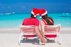 年轻夫妇后面看法在红色圣诞老人帽子的 库存照片