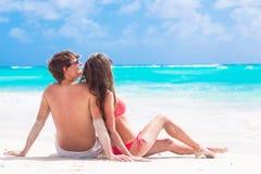 夫妇后面看法坐一个热带海滩  免版税库存图片