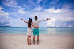 年轻夫妇后面看法涂了他们的胳膊 免版税库存图片