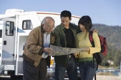 夫妇和资深父亲读书在RV之外映射 库存图片