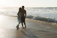 年轻夫妇喜欢走在一个朦胧的海滩在 图库摄影