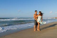 年轻夫妇喜欢走在一个朦胧的海滩在 库存照片