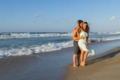 年轻夫妇喜欢走在一个朦胧的海滩在 免版税库存图片
