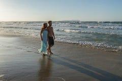 年轻夫妇喜欢走在一个朦胧的海滩在 免版税库存照片