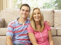 夫妇回家松弛沙发年轻人 免版税库存照片