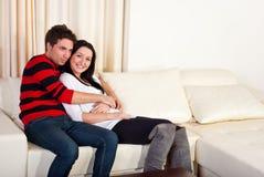 夫妇回家爱沙发年轻人 库存图片