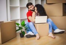 夫妇回家移动新的年轻人 坐和放松在unpac以后 免版税图库摄影