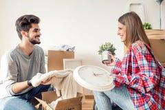 夫妇回家移动新的年轻人 打开箱子容器和清洗 库存图片