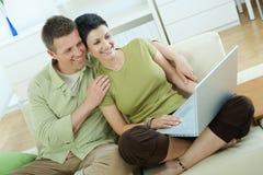 夫妇回家膝上型计算机使用 免版税库存照片