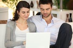 夫妇回家膝上型计算机使用 免版税库存图片