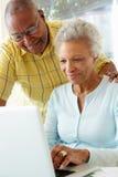 夫妇回家膝上型计算机前辈使用 免版税库存照片