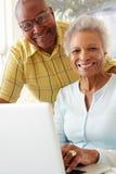 夫妇回家膝上型计算机前辈使用 免版税库存图片