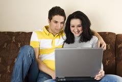 夫妇回家膝上型计算机年轻人 库存照片