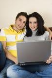 夫妇回家膝上型计算机 免版税图库摄影