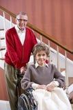 夫妇回家高级轮椅妇女 免版税库存照片