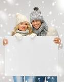 夫妇在一个冬天给拿着空白的委员会穿衣 图库摄影