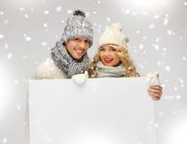夫妇在一个冬天给拿着空白的委员会穿衣 免版税库存图片