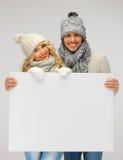 夫妇在一个冬天给拿着空白的委员会穿衣 库存照片