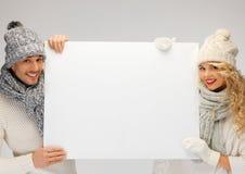 夫妇在一个冬天给拿着空白的委员会穿衣 免版税库存照片