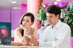 年轻夫妇在不互动的咖啡馆,但是在电话 免版税库存照片