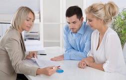 年轻夫妇在与一位银行家或顾问的一个日期退休的a 图库摄影