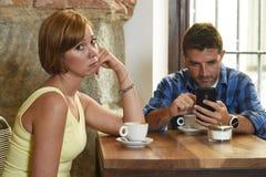 年轻夫妇在与互联网和手机上瘾者的咖啡店供以人员忽略沮丧的妇女 库存照片