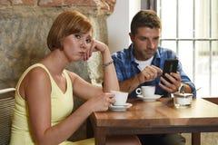 年轻夫妇在与互联网和手机上瘾者的咖啡店供以人员忽略沮丧的妇女 免版税库存照片