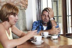年轻夫妇在与互联网和手机的咖啡店使忽略沮丧的人的妇女上瘾 免版税库存照片