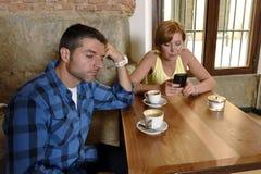 年轻夫妇在与互联网和手机的咖啡店使忽略沮丧的人的妇女上瘾 库存照片
