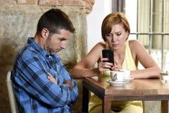 年轻夫妇在与互联网和手机的咖啡店使忽略沮丧的人的妇女上瘾 免版税库存图片