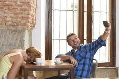 夫妇在与供以人员拍selfie照片忽略乏味哀伤和沮丧的妇女的手机上瘾者的咖啡店 免版税库存照片