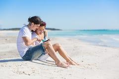 年轻夫妇在与数字式片剂的海边 库存图片
