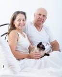 夫妇在与猫的床上 免版税库存照片